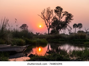 Sunset in the Okavango Delta with Makoros in front