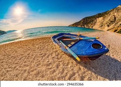 Sunset with Old Blue Boat on Empty Myrtos Beach on Kefalonia Island of Greece