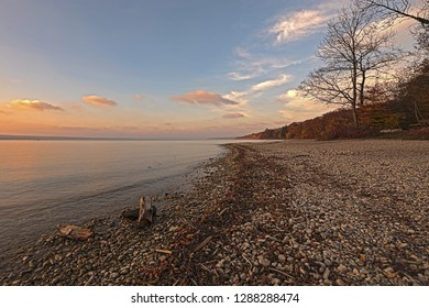 Sunset on the Ammersee, Bavaria,  Germany, Europe. Water, pebbles, tress and a beautiful sunlit sky