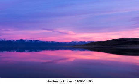Sunset on Antelope Island looking at mountain range with snow on top, pink sunset, and mountain range as a leading line and clouds reflecting off of the Great Salt Lake
