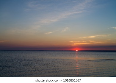 Sunset on beach on Baltic sea with calm water