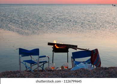 Sunset on the beach with BBQ, two camp chairs and a couple of glass of beer or wine