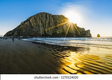Sunset on the beach, beautiful rays of sunshine, big rock in the sea, Morro Rock, California