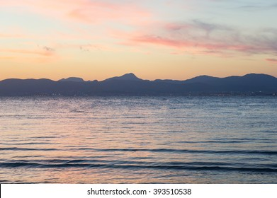 Sunset on the beach with beautiful sky, Majorca. Seaview sunset with beautiful pink sky. Summer sunset near mountains and sea, travel concept photography. Soft pink sunset with empty calm sea, Majorca