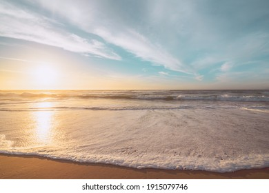 Sunset on the beach. Beautiful tranquil scene of empty sand beach, turquoise colored water, and cloudy sky