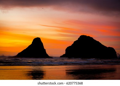 Sunset on the beach behind large rock formations in Oregon