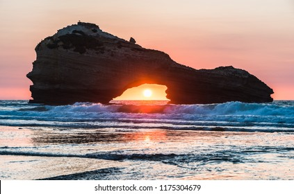 Sunset on a beach in Biarritz with the sun in the center of a rock's hole. Basque country of France.
