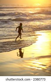 Sunset on the beach, boy running
