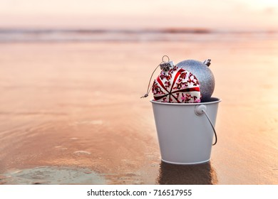 Sunset on the beach and Christmas decorations collected in a white bucket, holiday concept