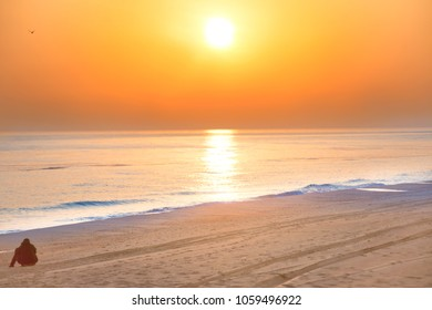 Sunset on the beach with long coastline, sun and dramatic sky