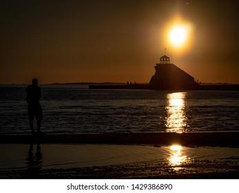 sunset on the beach Nallikari, Oulu,Finland and the lighthouse silhouette in the summer night sunshine