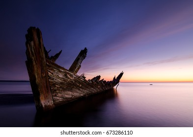 """Sunset on the beach with an old sailboat wreck.The """"Raketa"""" ship wreck on the Loksa beach in Estonia. The ship was built in 1949 in Finland"""
