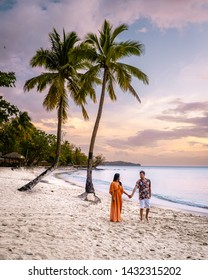 sunset on the beach with palm trees,  couple on beach watching sunset by the ocean of the tropical Island of Saint Lucia, Caribbean sunset at St Lucia beach wit men and woman walking on vacation