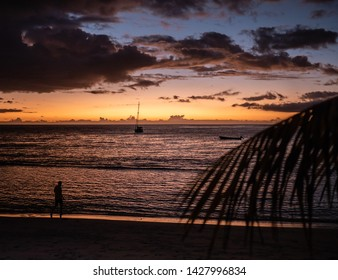 Sunset on the beach with people, boat, clouds and palmtree