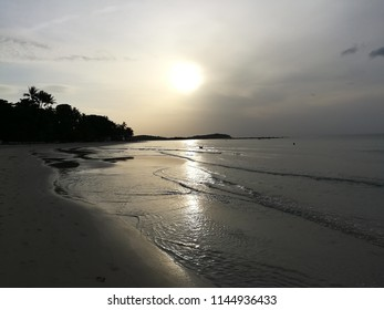 Sunset on the beach rising through the sky above the calm ocean with reflection into the water  white sand and alone every morning