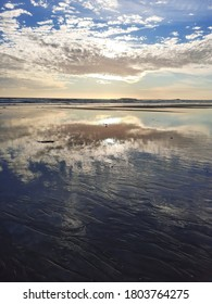 sunset on the beach of Sainte-Barbe, at low tide with reflection of the sky on the wet sand. southern Brittany Morbihan