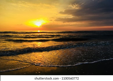 Sunset on the beach. The sun sets in the sea. Sunset on the North Sea coast. Bright sunset golden waves.