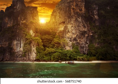 Sunset on beautiful beach in Thailand, Asia. Monumental rocks with green trees, sunset sky.