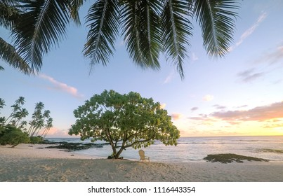 Sunset on beautiful empty tropical beach with deckchair and palm tree fronds at Lefaga, Matautu, Upolu Island, Western Samoa, South Pacific