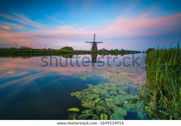 Sunset on a beautiful river in the Netherlands, in the background is an old windmill