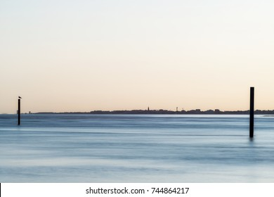 sunset on Bibione lagoon with Caorle silhouette background
