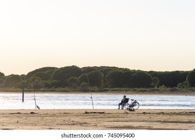 sunset on Bibione lagoon with an old fisherman fishing on the beach