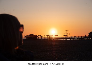 Sunset on the black sea. People walk along the beach and pier. Quiet, calm evening.