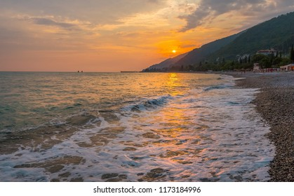 Sunset on the Black Sea with the sun. Georgia, Abkhazia. Colorful sunset with waves.