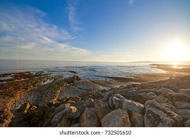Sunset on Blue ocean on stone beach. Background.