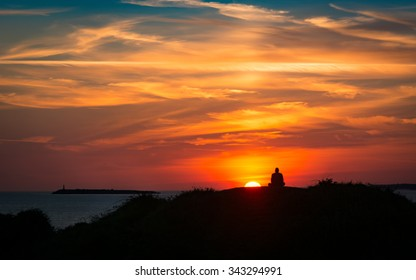 Sunset on the coast with a meditating man silhouetted against a colourful sky with clouds