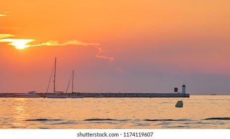Sunset on the coast of Porec in Croatia. In the background the lighthouse of the island Sveti Nikola.