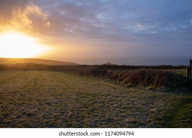 Sunset on a Cornish field with the Atlantic ocean in the background.