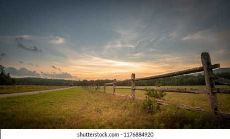 Sunset on a country meadow with a split rail fence