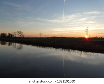 sunset on a dutch canal on the countryside of Groningen, leading to the northsea. Two dutch barges are moored here. A little ferry is the only way to a little house. Stunning contrails