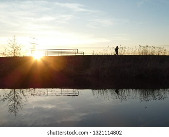 sunset on a dutch canal on the countryside of Groningen, leading to the northsea. Two dutch barges are moored here. Silhouette from a person.