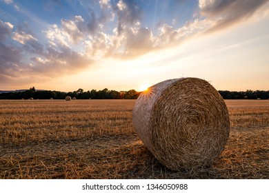 Sunset on a field of Straw after the harvest, with bales of Straw in the foreground