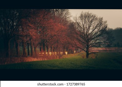 Sunset on fields and road, long exposure, blurry car lights