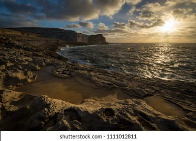Sunset on Fungus Rock on Malta Gozo. Dwejra Bay at the west coast of the Maltese Island of Gozo. Limestone rocky coast Mediterranean Sea.