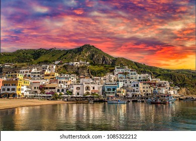 sunset on higgledy-piggledy piled houses on bay of Ischia island, Naples in Italy