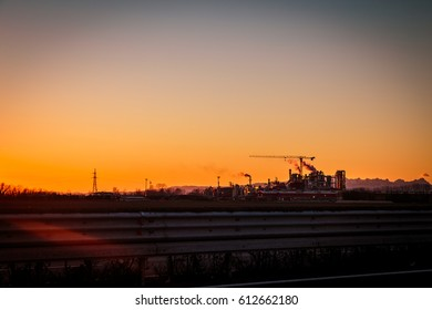 sunset on the highway in front of an industry
