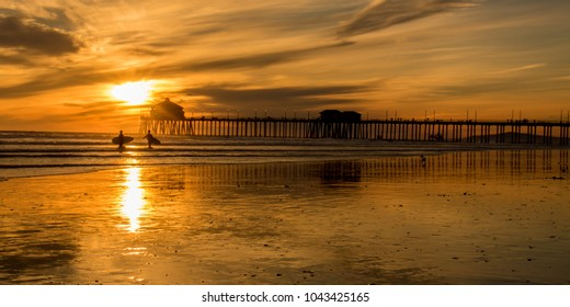 sunset on Huntington beach with pier and surfers in silhouette