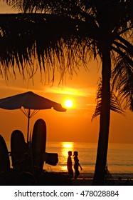 Sunset on Kuta beach, Bali, palm, sea and surfs
