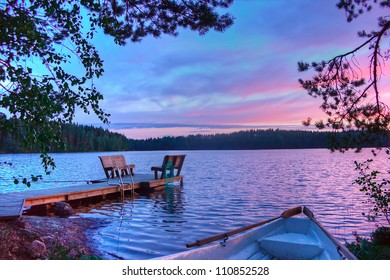 Sunset on the lake with a boat, trees, walkways and benches in Finland
