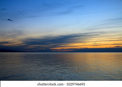 Sunset on the lake, calm water, clouds, pastel sky. Kyrgyzstan, Lake Issyk-Kul.