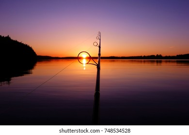 Sunset on a lake in Finland seen through a fishing rod ring on a warm and serene summer evening