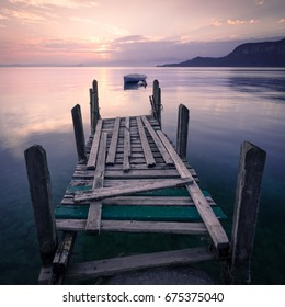 Sunset on Lake Garda, Italy. A silhouetted boat is reflected in the still lake waters beyond an old wooden jetty. Gentle hills are silhouetted in the distance.