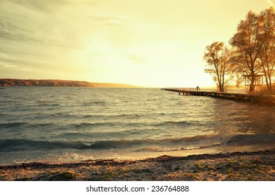 Sunset on a lake (Tollensesee) with a landing stage thereon stands a person.