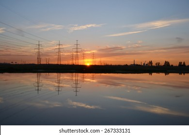 Sunset on the lake and transmission power line.