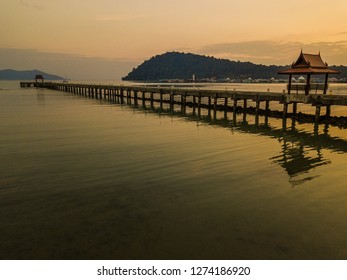 Sunset on a lonely pier. The most beautiful mountains of Thailand are in the background. The sun paints the blue sea to orange.