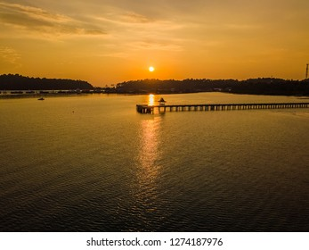 Sunset on a lonely pier. The most beautiful parts of Thailand in silhouette and the horizon are in the background. The sun paints the blue sea to orange